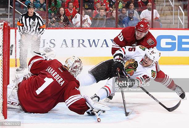 Viktor Stalberg of the Chicago Blackhawks crashes into goaltender Jason LaBarbera of the Phoenix Coyotes as he attempts to score during the third...