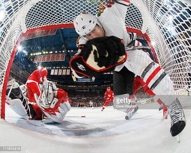 Viktor Stalberg of the Chicago Blackhawks crashes into the back of the net as Jimmy Howard of the Detroit Red Wings defends the goal during an NHL...