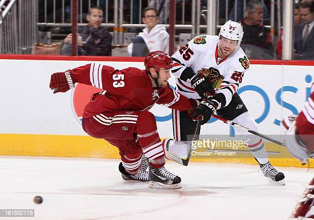 Viktor Stalberg of the Chicago Blackhawks passes the puck around Derek Morris of the Phoenix Coyotes during the NHL game at Jobingcom Arena on...