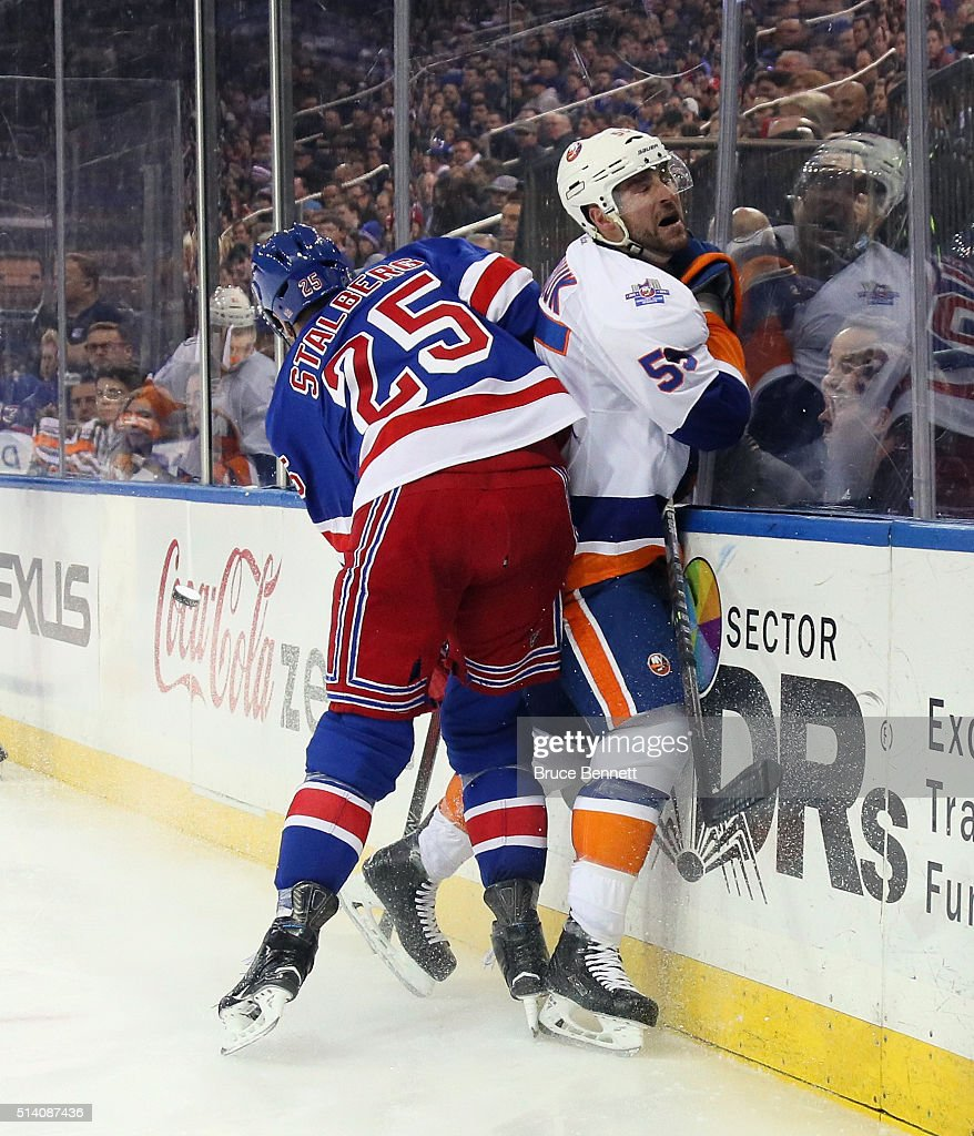 Viktor Stalberg #25 of the New York Rangers checks Johnny Boychuk #55 of the New York Islanders into the boards at Madison Square Garden on March 6, 2016 in New York City. The Islanders defeated the Rangers 6-4.
