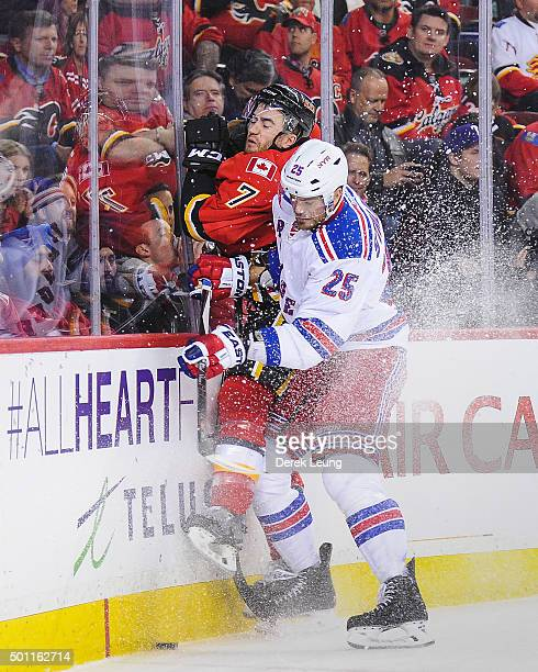 Viktor Stalberg of the New York Rangers checks TJ Brodie of the Calgary Flames during an NHL game at Scotiabank Saddledome on December 12 2015 in...