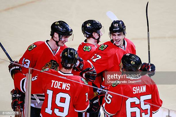 Viktor Svedberg and Trevor van Riemsdyk of the Chicago Blackhawks celebrate with teammates after Svedberg scored in the third period of the NHL game...