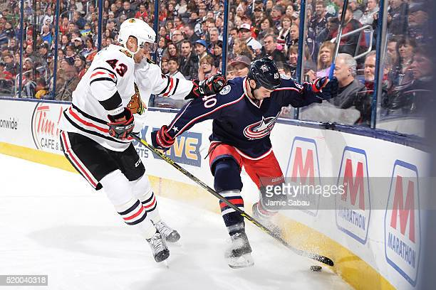 Viktor Svedberg of the Chicago Blackhawks and Jared Boll of the Columbus Blue Jackets battle for the puck against the boards during the first period...
