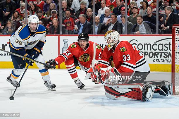 Viktor Svedberg of the Chicago Blackhawks reaches for the puck against Troy Brouwer of the St Louis Blues as goalie Scott Darling guards the net in...