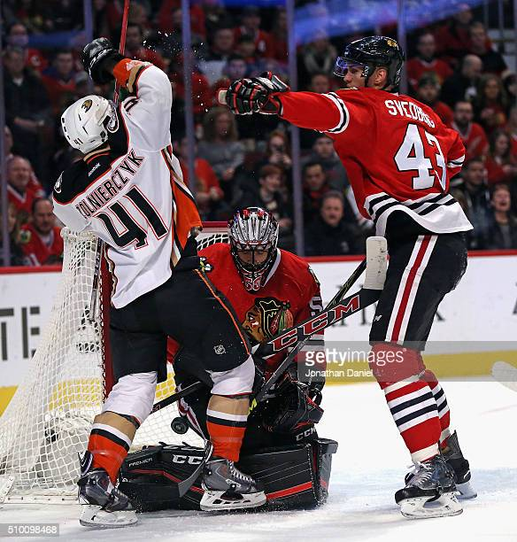 Viktor Svedberg of the Chicago Blackhawks shoves Harry Zolnierczyk of the Anaheim Ducks as Corey Crawford makes a save at the United Center on...