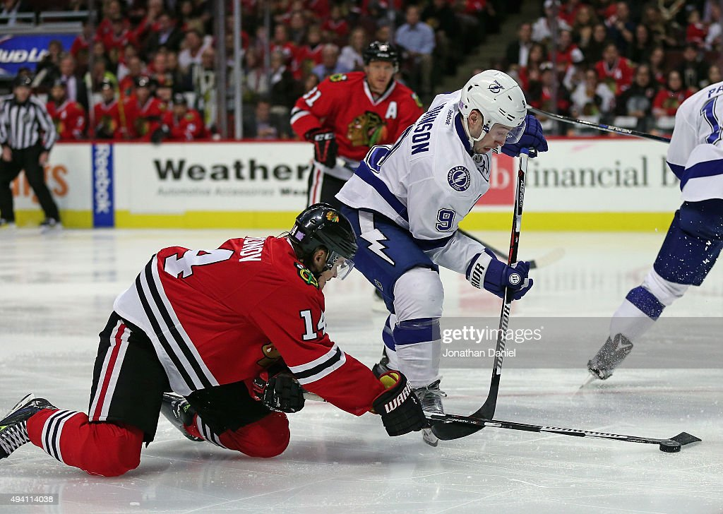 Viktor Tikhonov #14 of the Chicago Blackhawks knocks the puck away from Tyler Johnson #9 of the Tampa Bay Lightning at the United Center on October 24, 2015 in Chicago, Illinois.