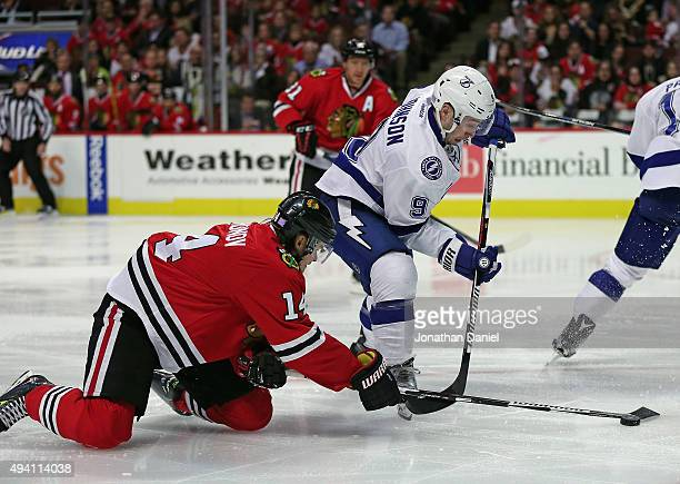 Viktor Tikhonov of the Chicago Blackhawks knocks the puck away from Tyler Johnson of the Tampa Bay Lightning at the United Center on October 24 2015...
