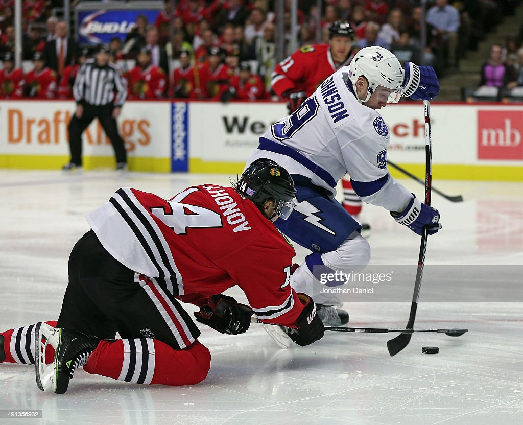 Viktor Tikhonov #14 of the Chicago Blackhawks knocks the puck away from Tyler Johnson #9 of the Tampa Bay Lightning at the United Center on October 24, 2015 in Chicago, Illinois. The Blackhawks defeated the Lightning 1-0 in overtime.