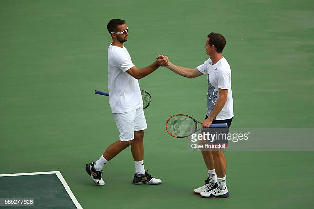 Viktor Troicki of Serbia and Andy Murray of Great Britain embrace during a practice session ahead of the Rio 2016 Olympic Games at the Olympic Tennis...