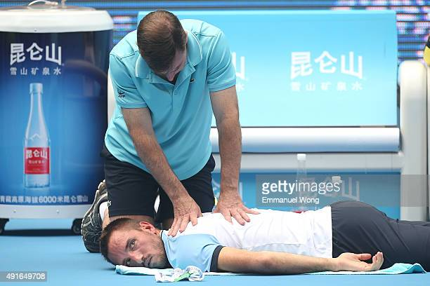 Viktor Troicki of Serbia receives treatment during the match against YenHsun Lu of Taipei during the day five of the 2015 China Open at the China...