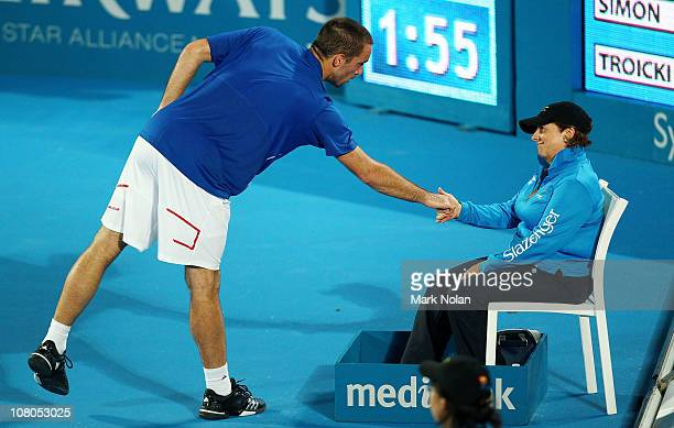 Viktor Troicki of Serbia shakes the hand of a line judge after a foot fault call in his match against Gilles Simon of France during day seven of the...