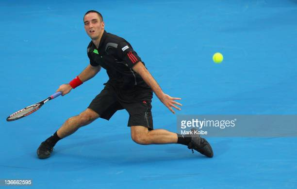 Viktor Troicki of Serbia stretches to play a forehand in his second round match against Lleyton Hewitt of Australia during day three of the 2012...