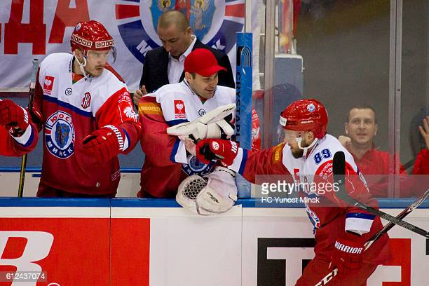 Viktor Turkin of Yunost Minsk celebrates scoring with teammates Alexander Tryanichev and Jesse Niinimaki during the 2nd period of Champions Hockey...