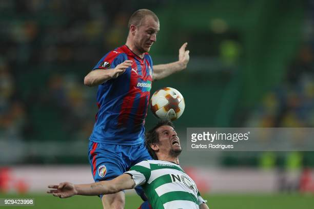 Viktoria Plzen forward Michal Krmencik from Czech Republic vies with Sporting CP defender Fabio Coentrao from Portugal for the ball possession during...