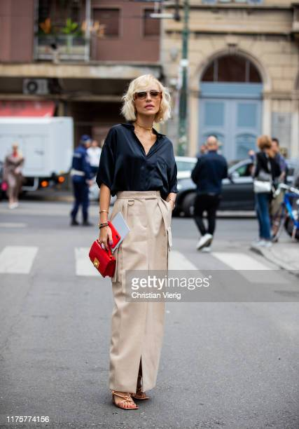 Viktoria Rader is seen wearing beige skirt red bag black blouse laced sandals outside the Max Mara show during Milan Fashion Week Spring/Summer 2020...