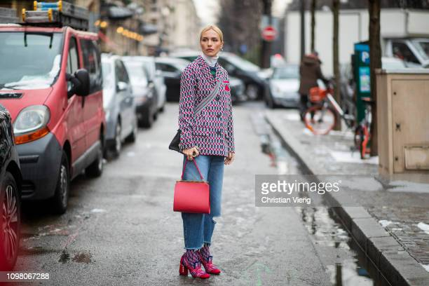 Viktoria Rader is seen wearing ripped denim jeans blazer jacket with pattern turtleneck red bag shoes socks outside Stephane Rolland during Haute...