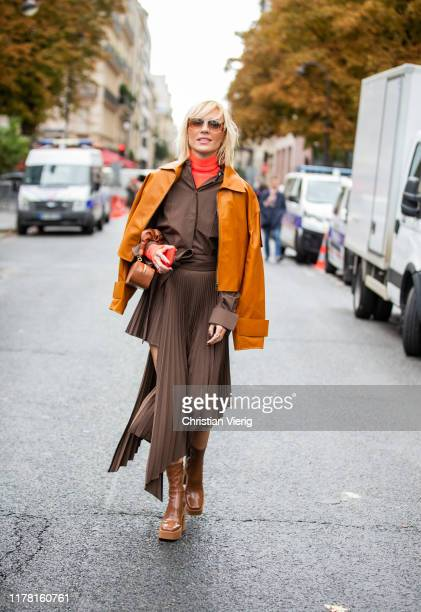 Viktoria Rader seen wearing orange brown cropped kacet, brown asymmetric pleated skirt and button shirt outside Akris during Paris Fashion Week...