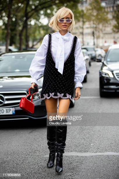 Viktoria Rader wearing a white shirt black decorated mini dress red bag and black boots is seen outside the Redemption show during Paris Fashion Week...