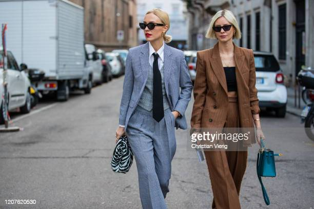 Viktoria Rader wearing grey suit bag with zebra print and Lisa Hahnbueck is seen wearing brown striped suit Hermes bag outside Max Mara during Milan...