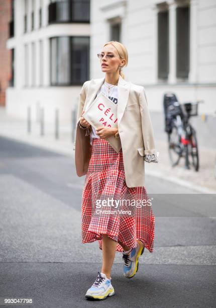 Viktoria Rader wearing red plaid skirt asymmetrical sneaker Celine clutch and blazer seen outside William Fan during the Berlin Fashion Week July...