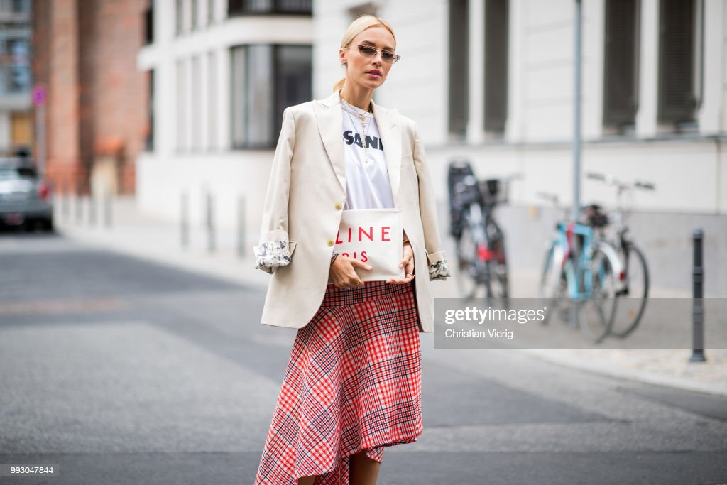Viktoria Rader wearing red plaid skirt, asymmetrical sneaker, Celine clutch and blazer seen outside William Fan during the Berlin Fashion Week July 2018 on July 6, 2018 in Berlin, Germany.