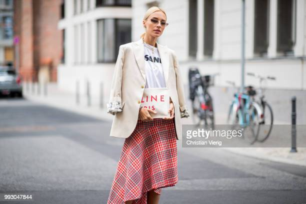 Viktoria Rader wearing red plaid skirt, asymmetrical sneaker, Celine clutch and blazer seen outside William Fan during the Berlin Fashion Week July...