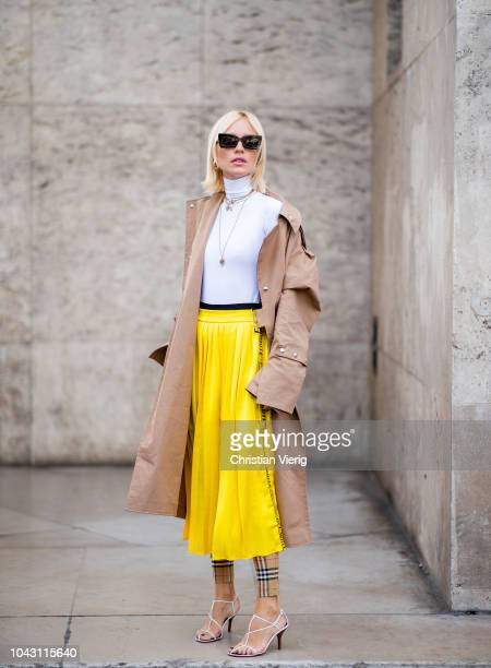 Viktoria Rader wearing trench coat yellow pleated skirt white turtleneck Burberry pants sandals is seen outside Issey Miyake during Paris Fashion...