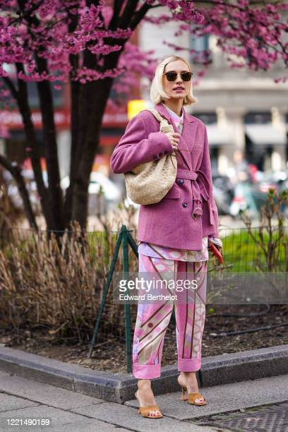 Viktoria Rader wears hair pins, sunglasses, a pink wool jacket, a Bottega Veneta woven leather bag, colorful pastel colored pants, brown shoes,...