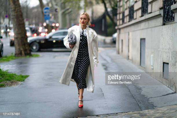 Viktoria Rader wears long bejeweled earrings, a white long coat, a black and white zebra print puff bag, a black and white dress with polka dots, red...