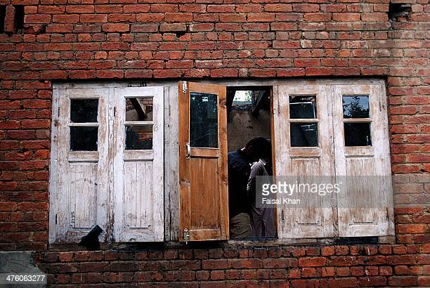 Vilagers inspect the destroyed house in yachgosa Shopian,Kashmir where two militants were killed in a 19 hour long fierce gun-battle between...