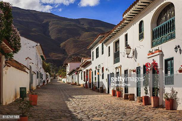 villa de leyva, colombia: looking up calle 14 in the early morning sunlight towards the mountains in the historic 16th century andean town - cafe de colombia stock pictures, royalty-free photos & images