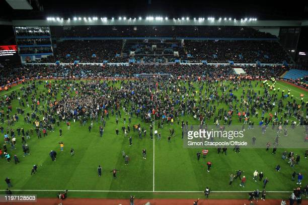 Villa fans invade the pitch as they celebrate victory after the Carabao Cup Semi Final match between Aston Villa and Leicester City at Villa Park on...