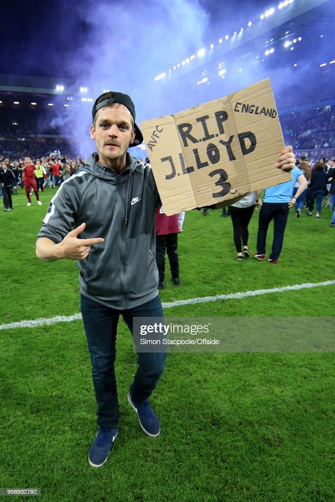 Villa fans invade the pitch to celebrate victory as one of them holds a sign in tribute to the late Jlloyd Samuel at the end of the Sky Bet Championship Play Off Semi Final Second Leg match between Aston Villa and Middlesbrough at Villa Park on May 15, 2018 in Birmingham, England.