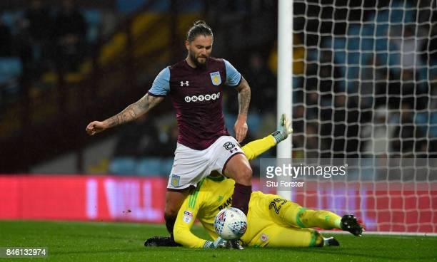 Villa player Henri Lansbury goes down under the challenge of Middlesbrough goalkeeper Darren Randolph during the Sky Bet Championship match between...