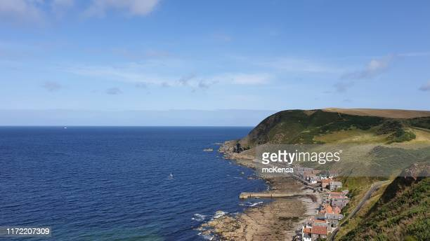 village at bottom of cliff with sea, blue sky and copy space - aberdeenshire stock pictures, royalty-free photos & images