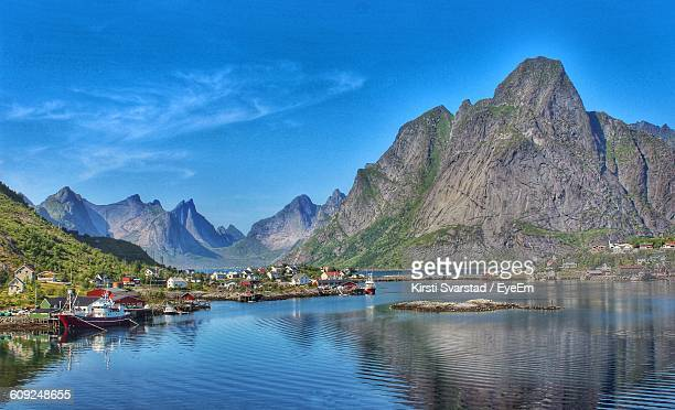 Village By Sea And Mountains Against Sky At Lofoten
