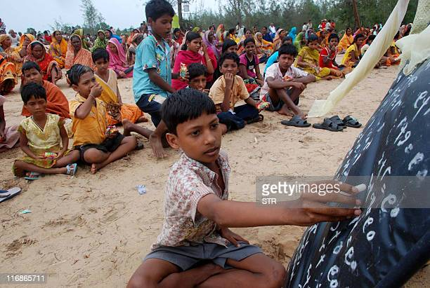 Village children continue with their lessons as villagers sit along the entry point to prevent policemen and officials from entering their land at...
