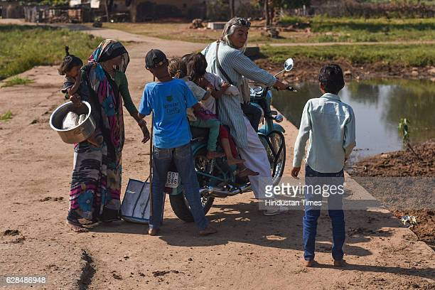 Village children riding pillion on bike with German community activist and author Ulrike Reinhard on October 26, 2016 in Janwaar, India. Thanks to a...