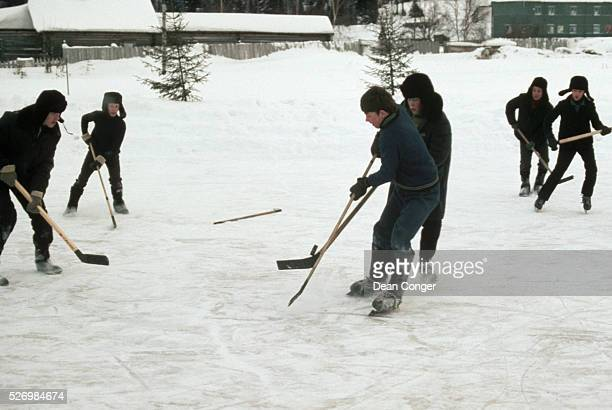 Village children some with skates and some without play a game of hockey on a frozen patch of ice | Location Khanty Mansiysk Siberia USSR