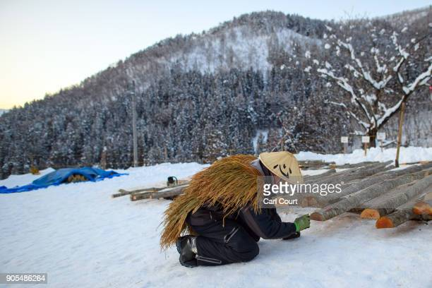 A village man wearing a traditional conical hat and straw cape checks logs that will be used in the construction of the shrine as preparations are...