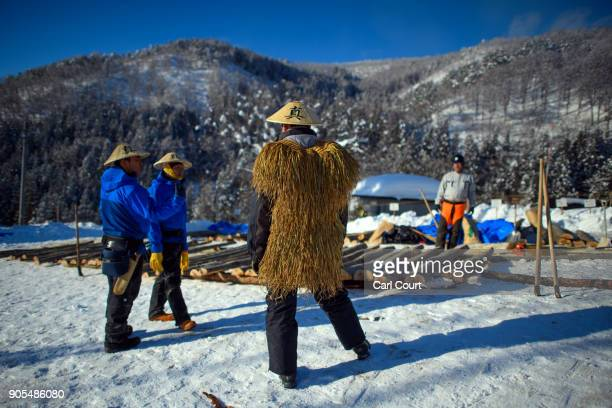 A village man wearing a traditional conical hat and straw cape looks on as logs are prepared for use in the construction of the shrine ahead of the...