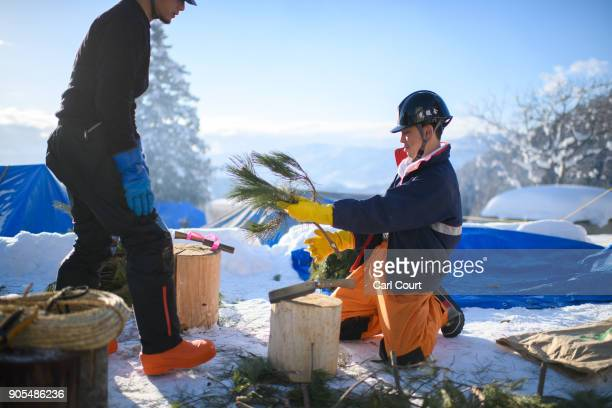 Village men prepare pine branches as they work on building a shrine during preparations for the Nozawaonsen Dosojin Fire Festival on January 14 2018...