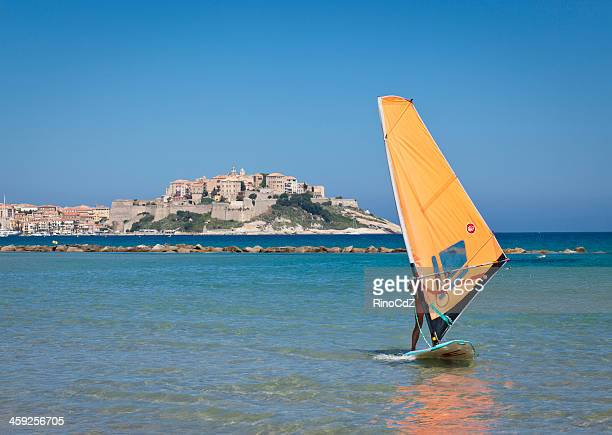 village of calvi with a windsurf in the foreground - corsica stock photos and pictures