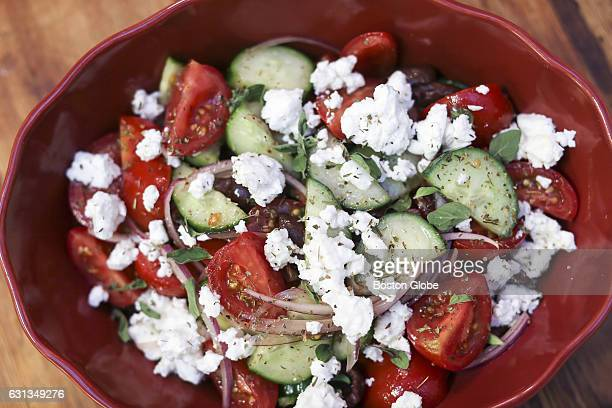 A village salad with cucumbers tomatoes olives feta red wine vinegar and oregano sits on a table eat Doretta Taverna in Boston on Oct 5 2015