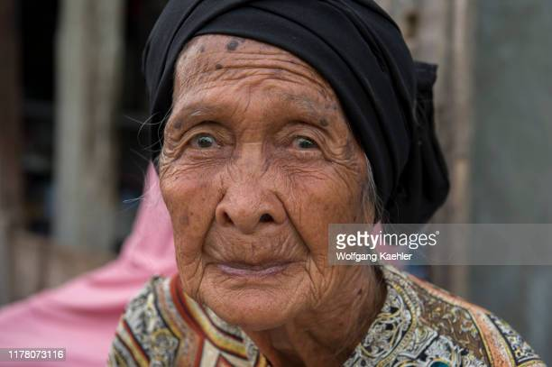 Village scene with a portrait of an elderly woman in the Bajau Sea Gypsy village on Bungin Island, famous for living in stilt houses above the water...
