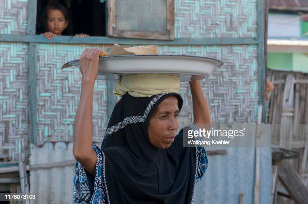 Village scene with a woman carrying a plate on her head in the Bajau Sea Gypsy village on Bungin Island, famous for living in stilt houses above the...