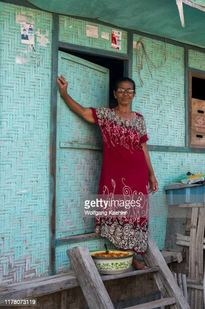 Village scene with a woman in front of her bamboo house in the Bajau Sea Gypsy village on Bungin Island, famous for living in stilt houses above the...