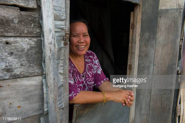 Village scene with a woman looking out of a window of a house in the Bajau Sea Gypsy village on Bungin Island, famous for living in stilt houses...