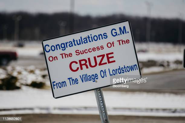 A village sign congratulating General Motors Co for the success of its Chevrolet Cruze vehicles stands on display near the GM Lordstown production...