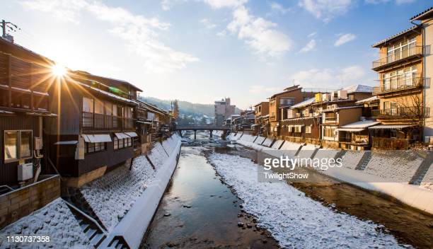 village snow sunrise at takayama with red wooden bridge and stream water, japan - takayama city stock pictures, royalty-free photos & images